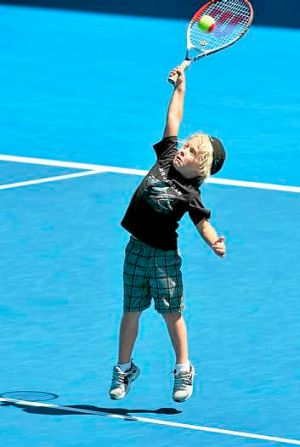 Cruz Hewitt takes to the court as his father, Lleyton, takes a break at training.