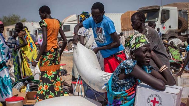 People receive food aid and other items such as soap, plastic mats and buckets near Bor.