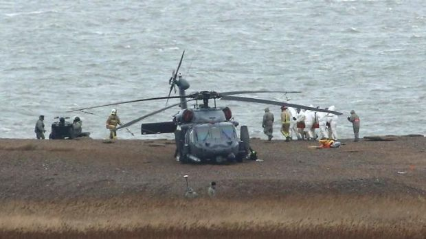 The recovery effort ... emergency services attend the scene after a US Air Force helicopter crashed on marshland near ...