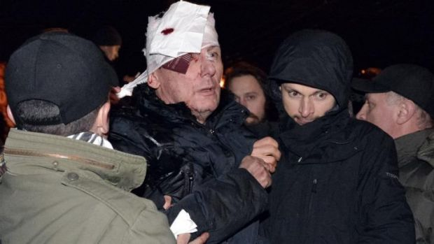 Bloodied: Ukrainian opposition leader Yuri Lutsenko is taken from the scene of protests in Kiev on Saturday morning.