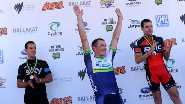 Simon Gerrans celebrates his win on the podium while Cadel Evans (right - second) and Richie Porte (third) look on.