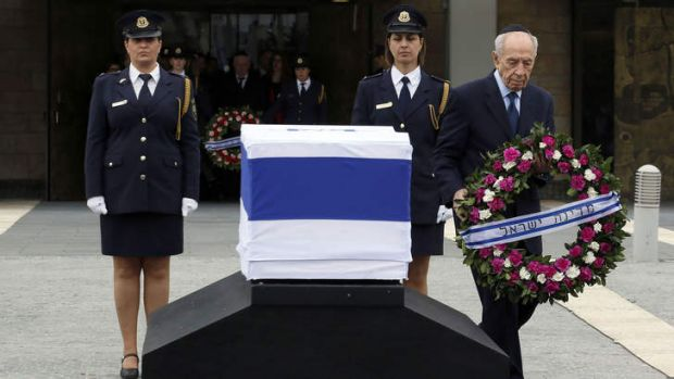Israeli President Shimon Peres lays a wreath by the coffin of former prime minister Ariel Sharon at the Israeli ...
