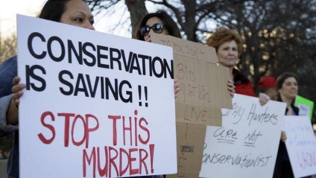 Veronica Rodriguez, left, of Garland Texas, stands with nearly 40 others protesting outside the Dallas Safari Club's ...