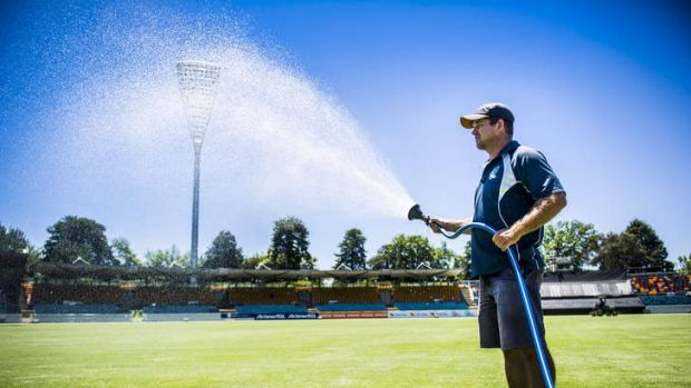 Brad Bandam, Head curator at Manuka Oval waters the pitch before the PM's XI.