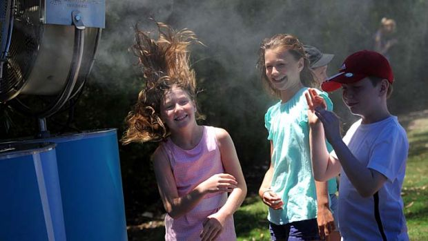 Searing sun: Young tennis fans cool down during day one of the 2014 Australian Open at Melbourne Park.