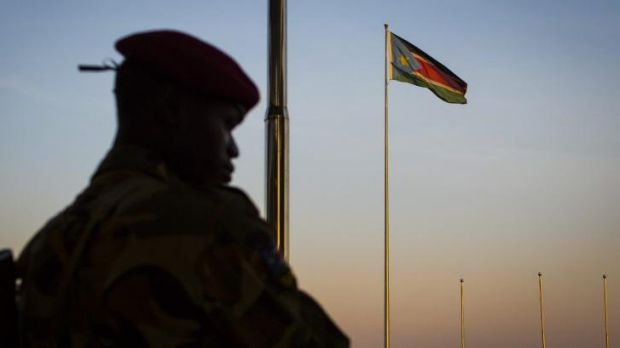 A South-Sudanese government soldier stands guard as a South Sudanese flag flies in the background in Juba, South Sudan.