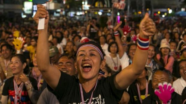 Anti-government protesters cheer during the first day of a mass demonstration at a downtown intersection in Bangkok, ...