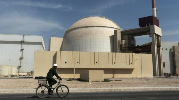 A worker rides a bicycle in front of the reactor building of the Bushehr nuclear power plant in Iran.