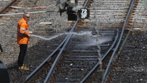 Metro staff hose down the hot railway tracks near Southern Cross Station.
