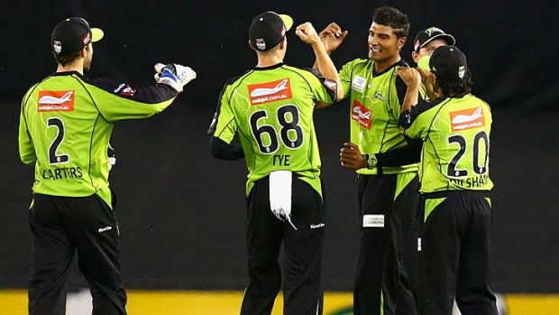 Sydney Thunder's Gurinder Sandhu celebrates after taking a catch off his own bowling to dismiss Peter Nevill of the ...