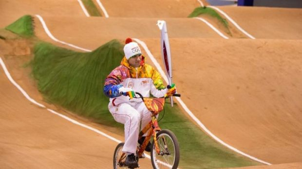 Olympic torch bearer Evgeniy Komarov rides a bicycle with an Olympic torch at a velodrome during the torch relay in ...