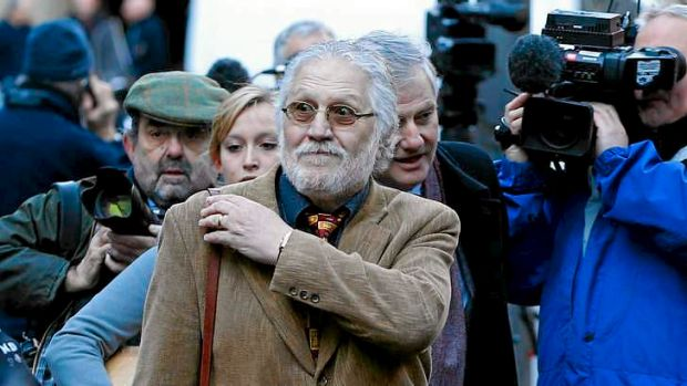 British radio jockey Dave Lee Travis, centre, arrives for the start of his trial in London.