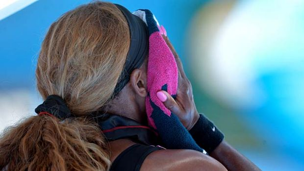 Serena Williams wipes her face with a towel during her second-round match against Vesna Dolonc.