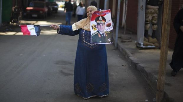 An Egyptian woman dances in front of a polling station holding a poster of General Abdel-Fattah al-Sisi.