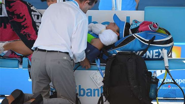 Zheng Jie's blood pressure is checked while she is treated for a heat-related illness during a medical time-out in her ...
