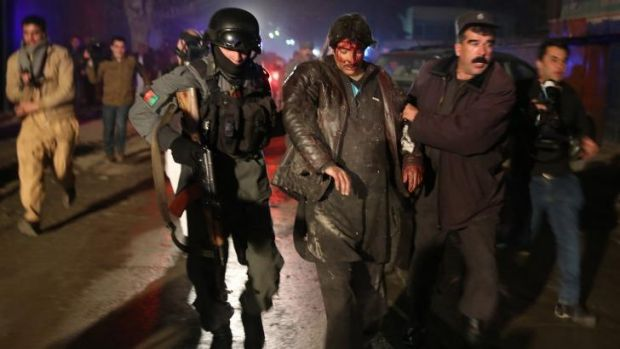 Suicide attack: Afghan police forces help an injured man at the site of the explosion.