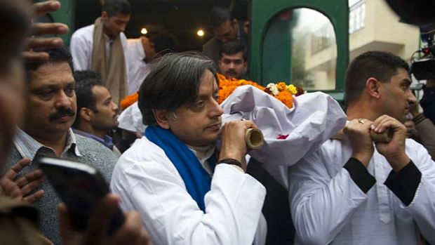 Indian MP Shashi Tharoor, centre, with relatives and friends as they carry the body of Tharoor's wife Sunanda to the ...