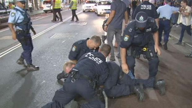 Police detain an alleged brawler on George Street outside the Ivy nightclub.