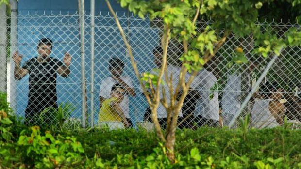 Asylum seekers  sit behind the wire of the Manus Island detention centre in Papua New Guinea.