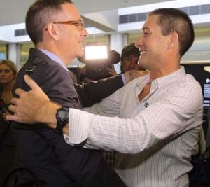 Haking off the dust of Dubai: Marcus Lee, right, embraces his lawyer John Sneddon.