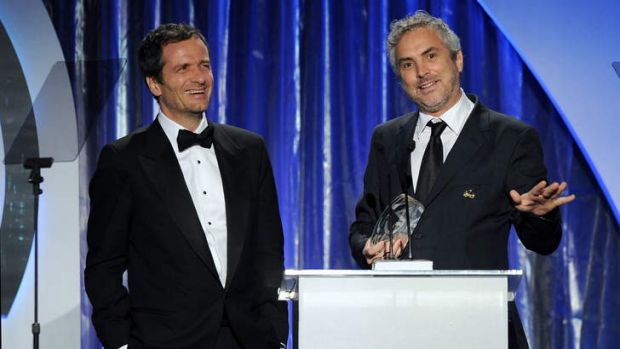 <i>Gravity</i> producer David Heyman (left) and director-producer Alfonso Cuaron accept the Darryl F. Zanuck Award for ...