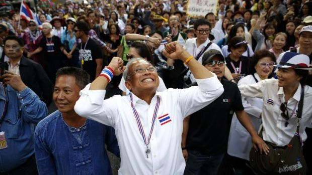 Protest leader Suthep Thaugsuban greets anti-government protesters as he marches through central Bangkok.