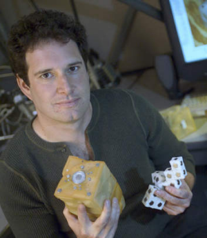 Hod Lipson with actual modular cubes used to make a self-replicating robot and small toy cubes he uses to illustrate the ...