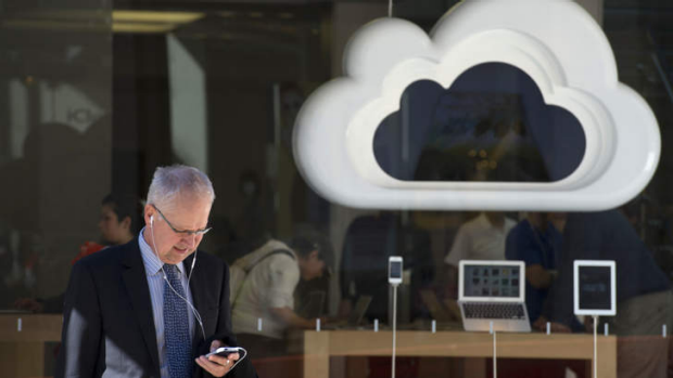 A man uses an Apple Inc. iPhone in front of a store in San Francisco, California, U.S.