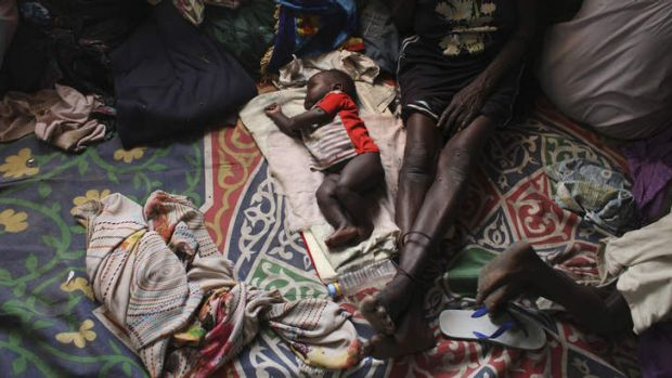 A baby sleeps next to a woman in a Catholic church in Malakal, South Sudan.