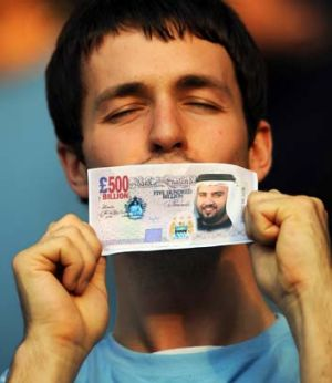 A Manchester City fan holds a fake British pound note with the face of Sheikh Mansour bin Zayed Al Nahyan after he ...