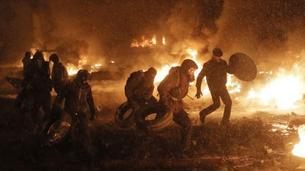 Protesters throw tires in a fire as they clash with police in central Kiev, Ukraine.