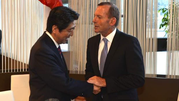 Pressing the flesh: Japanese Prime Minister Shinzo Abe meets Tony Abbott in Davos at the four-day World Economic Forum.