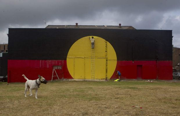 Members of the local community help re-paint the Aboriginal flag on the back of the Elouera-Tony Mundine Gym.