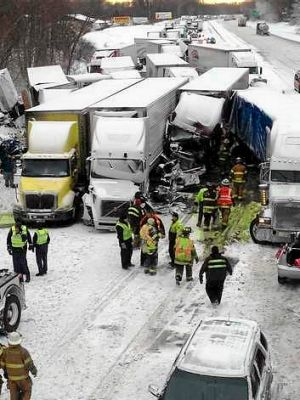 Trucks and passenger vehicles block eastbound Interstate 94 following a massive crash that killed three people and ...