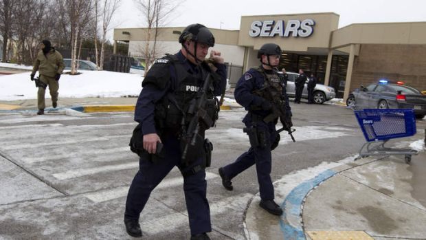 Police move in from a parking lot to the Mall in Columbia after reports of a multiple shooting.