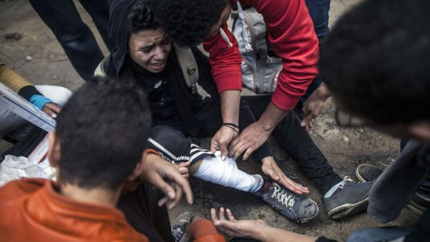Egyptian anti-government protesters take care of a comrade injured by a rubber bullet fired by police during clashes in ...