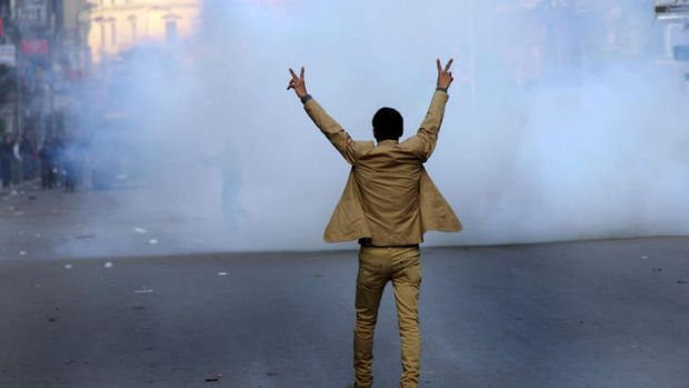 A supporter of the Egyptian government flashes the sign for victory during clashes with Muslim Brotherhood supporters in ...