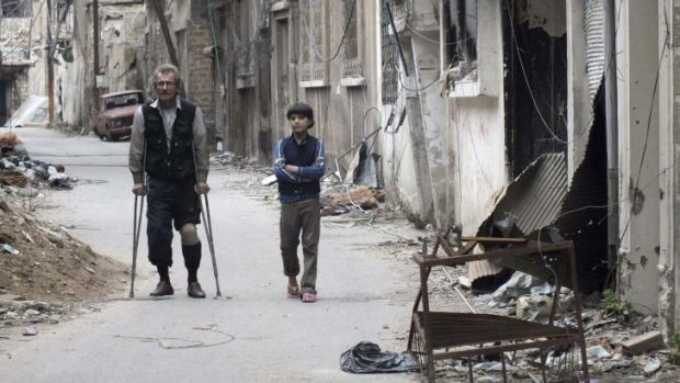 Ceasefire on the table: Residents walk by damaged buildings in the besieged area of Homs.