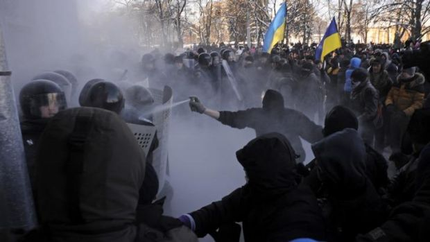 Clashes: A protester uses tear gas against riot police in Chernihiv, about 150 kilometres north of Kiev.