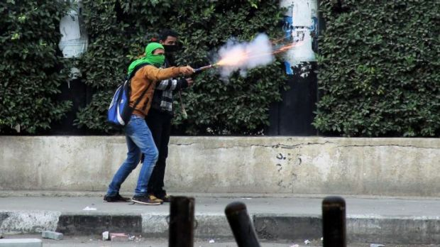 Clashes: A Muslim Brotherhood supporter aims fireworks at supporters of the Egyptian government in Cairo.