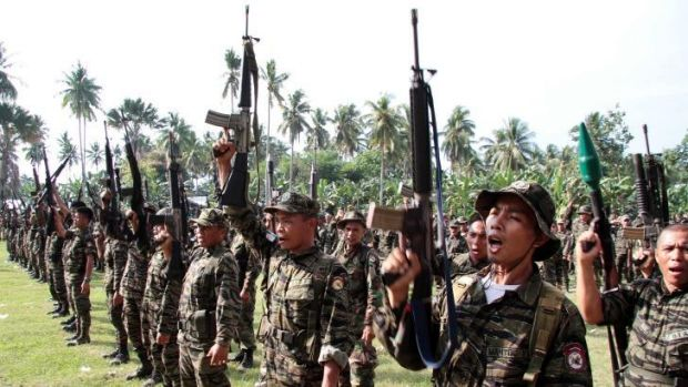 Members of the Moro Islamic Liberation Front rebels raising their rifles during a ceremony in 2012.