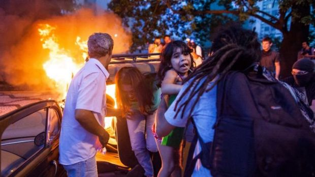 Unrest: Bystanders help a family away from a burning car during a fiery protest in Sao Paulo.