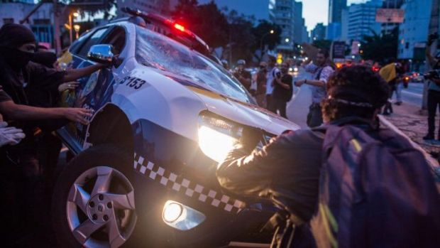 Brazilian protesters destroy a police vehicle during demonstrations against the staging of the upcoming 2014 World Cup ...