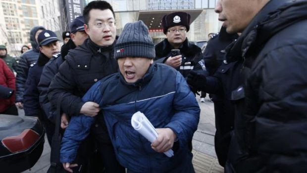 Chaotic scenes: A plain-clothes policeman escorts Zhang Qingfang, the lawyer of Xu Zhiyong, to a police car.