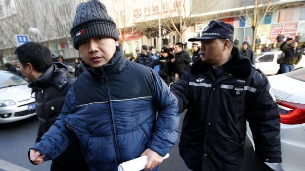 Policemen escort Zhang Qingfang, the lawyer of Xu Zhiyong, away from journalists after Xu's trial.
