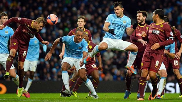 Manchester City's Argentine striker Sergio Aguero (centre) heads the ball towards goal during the match against Watford ...