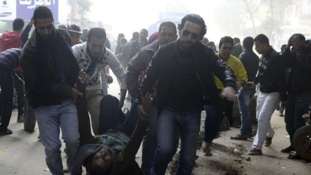 Demonstrators carry an injured Muslim Brotherhood supporter who was shot during clashes in Cairo.