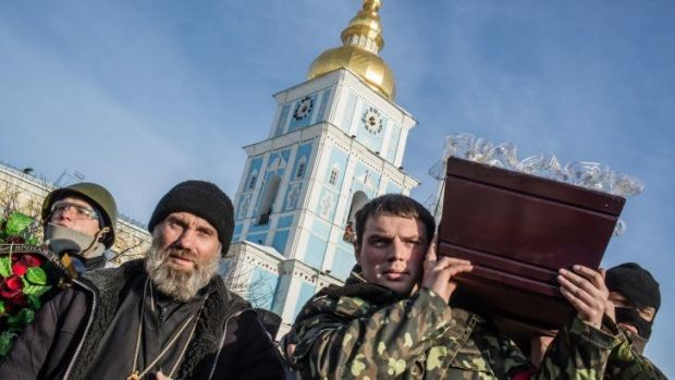 Men carry a casket containing the body of an anti-government protester killed in clashes with police in Kiev.