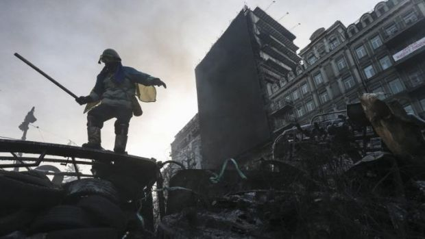 An anti-government protester stands on a barricade at the site of clashes with riot police in Kiev.