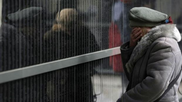 A Hungarian woman at the wall of victims at the Holocaust Museum in Budapest.